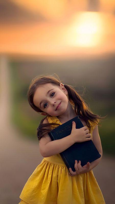 little cute girl with book Wallpaper